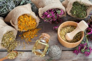 Healing herbs in hessian bags, wooden mortar with chamomile and essential oil on rustic table, herbal medicine.