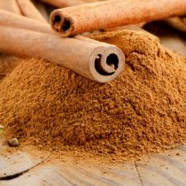 Cinnamon sticks and powder on wooden table. Selective focus