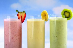 Assorted fruit and berry smoothies on blue sky background