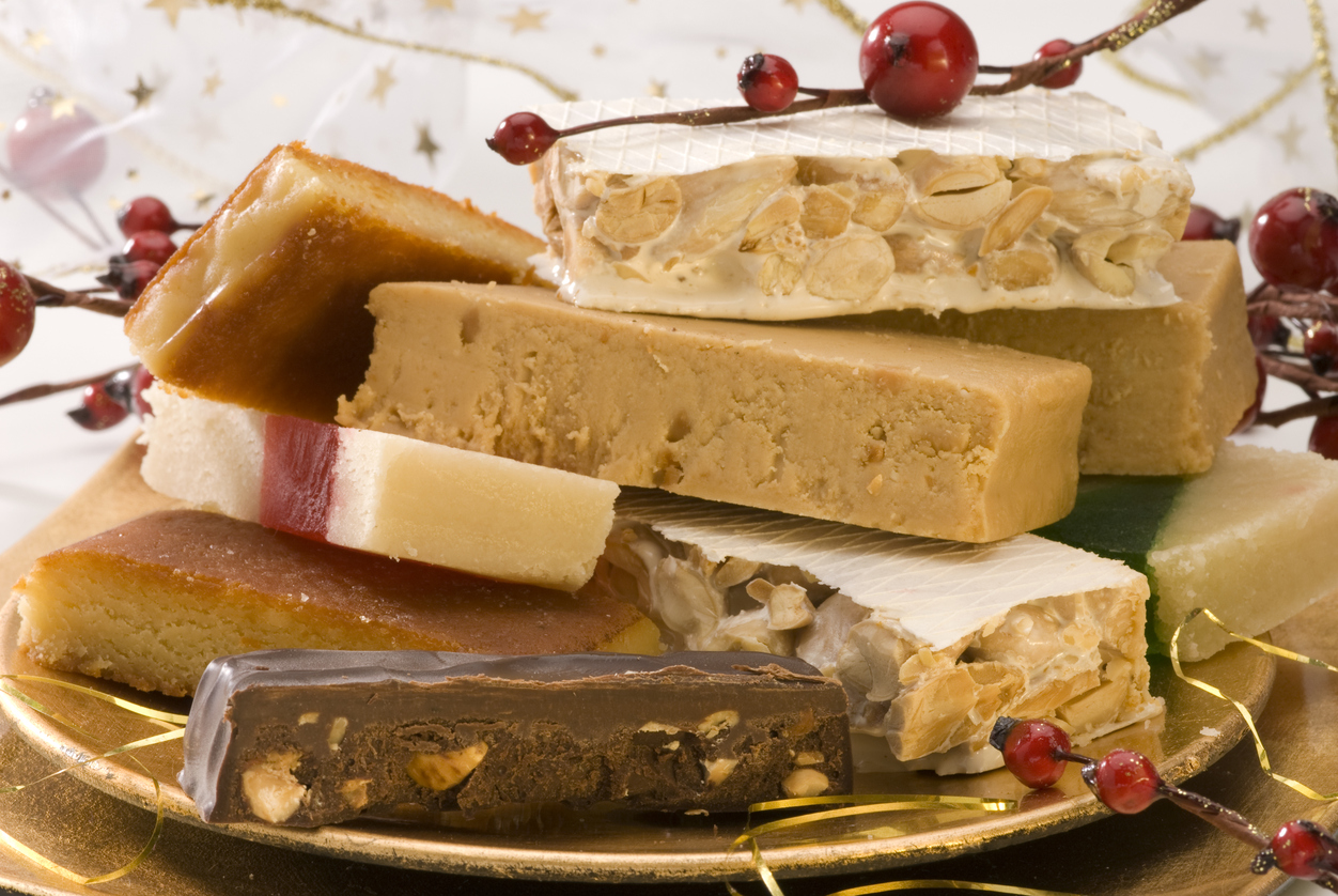 Typical spanish Christmas nougat in a golden plate. Selective focus.