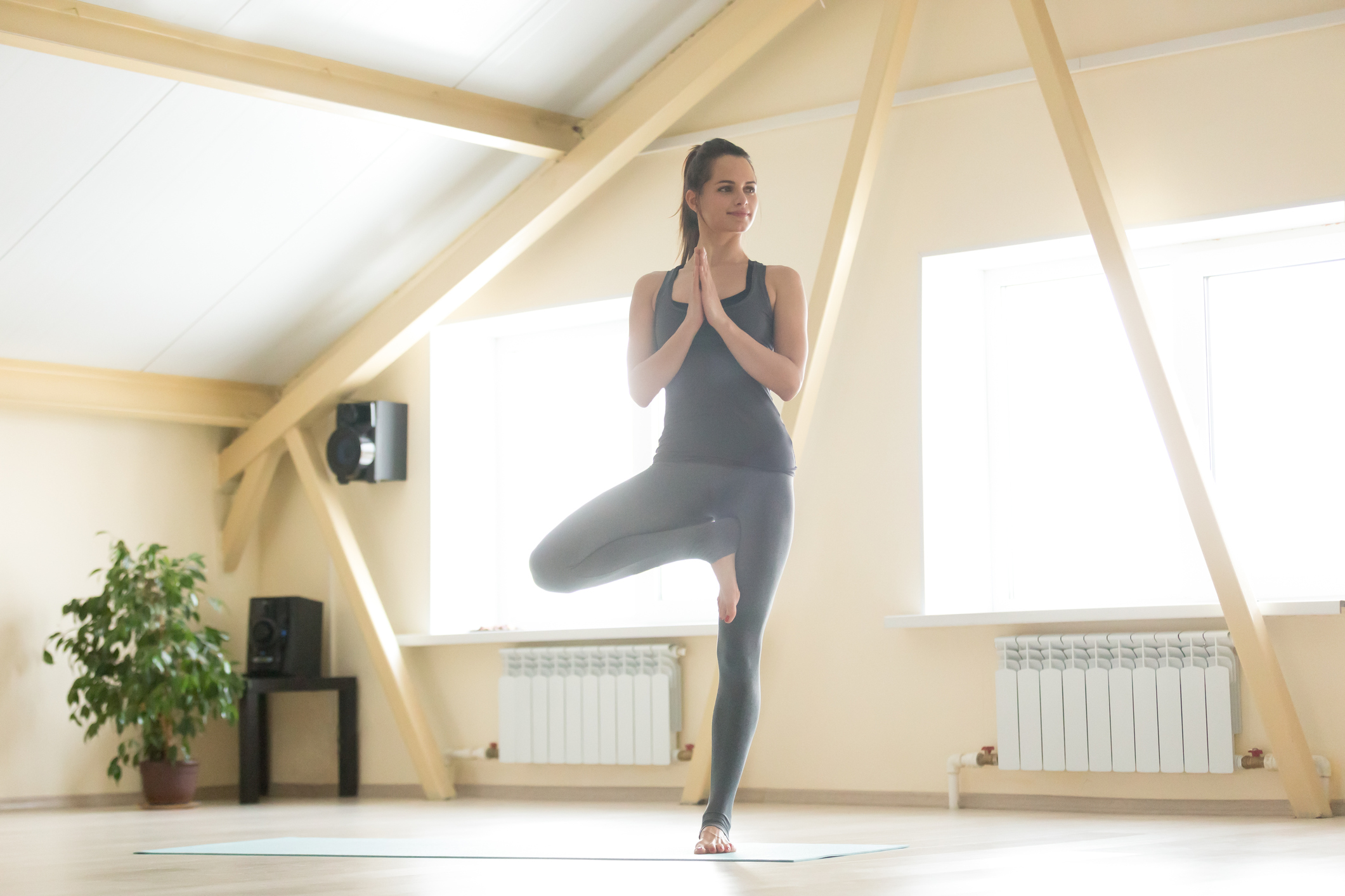 Young attractive woman practicing yoga, standing in Vrksasana exercise, Tree pose, working out, wearing sportswear, grey tank top, pants, indoor full length, home interior background